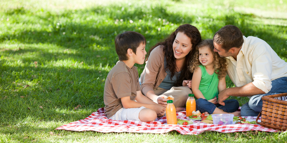 Parents with their two kids having a picnic on a blanket