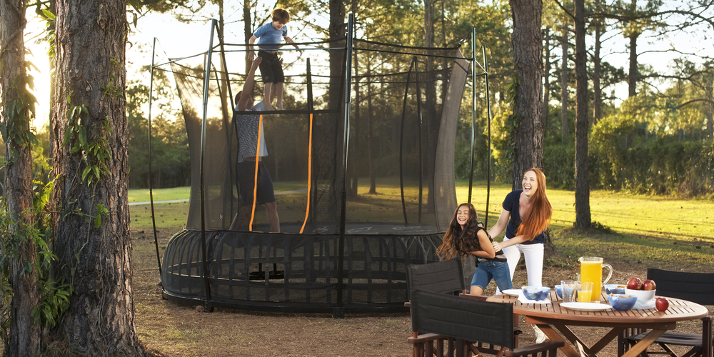 Kids bouncing on a Vuly trampoline while parents watch sitting down