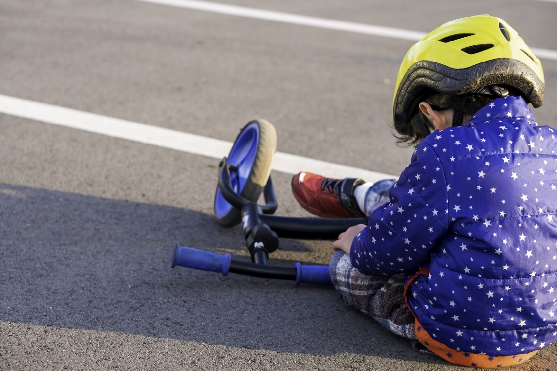 Child sitting on the ground with their balance bike