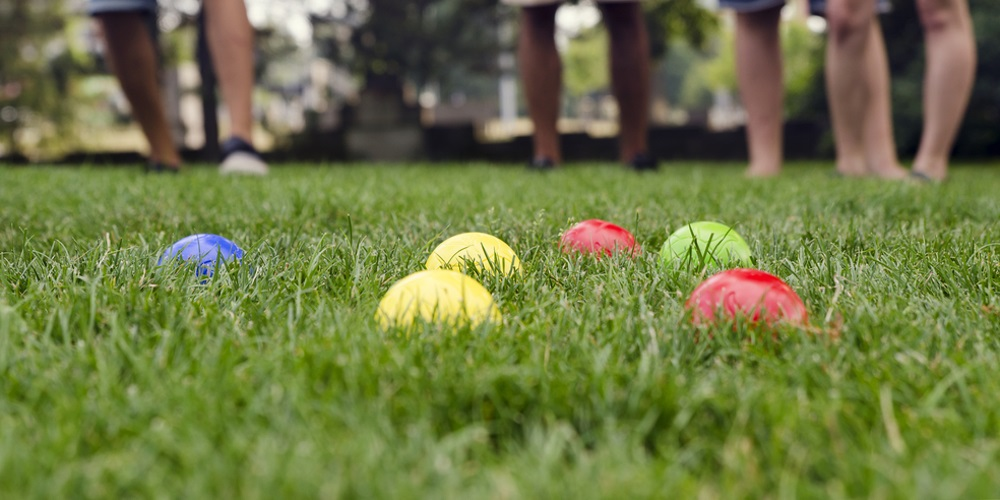 Coloured balls laying in lawn grass
