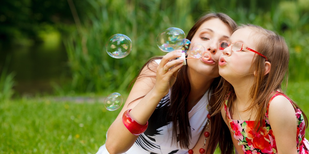 Woman and girl blowing bubbles together