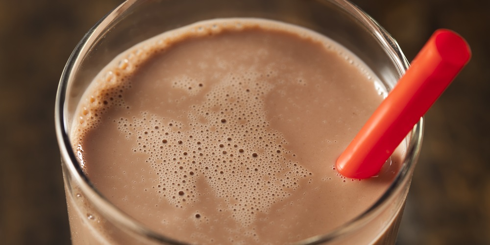 Chocolate milk in a glass with a red straw
