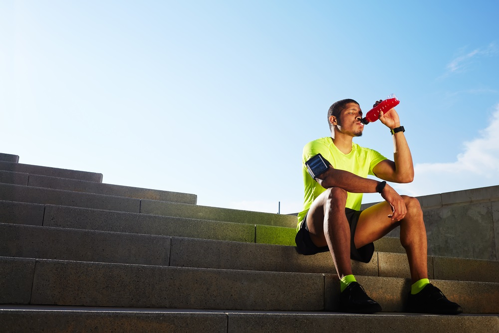 Man in exercise gear sitting on steps drinking a sports drink