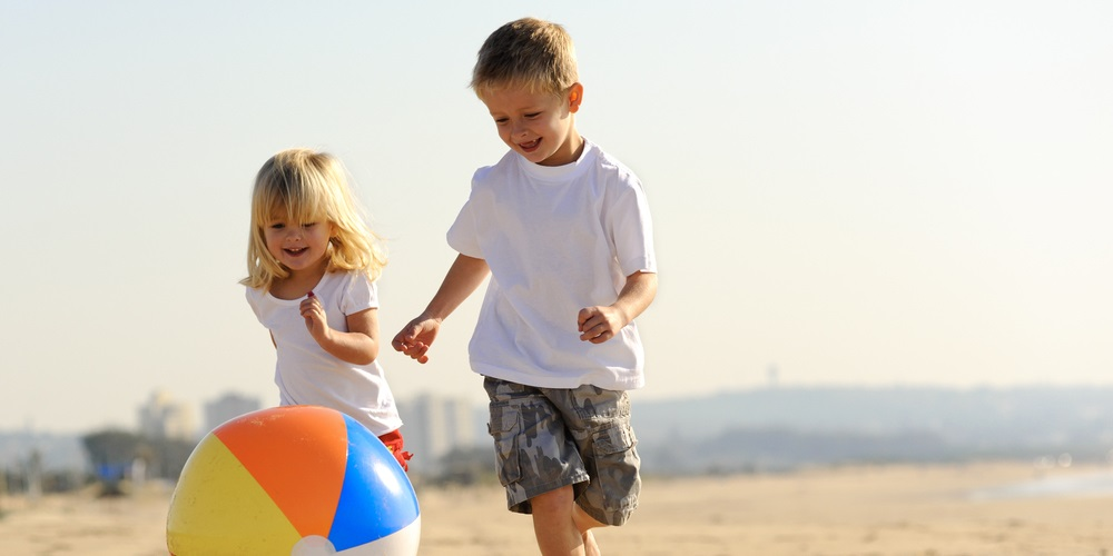 Girl and boy chasing beach ball across sand