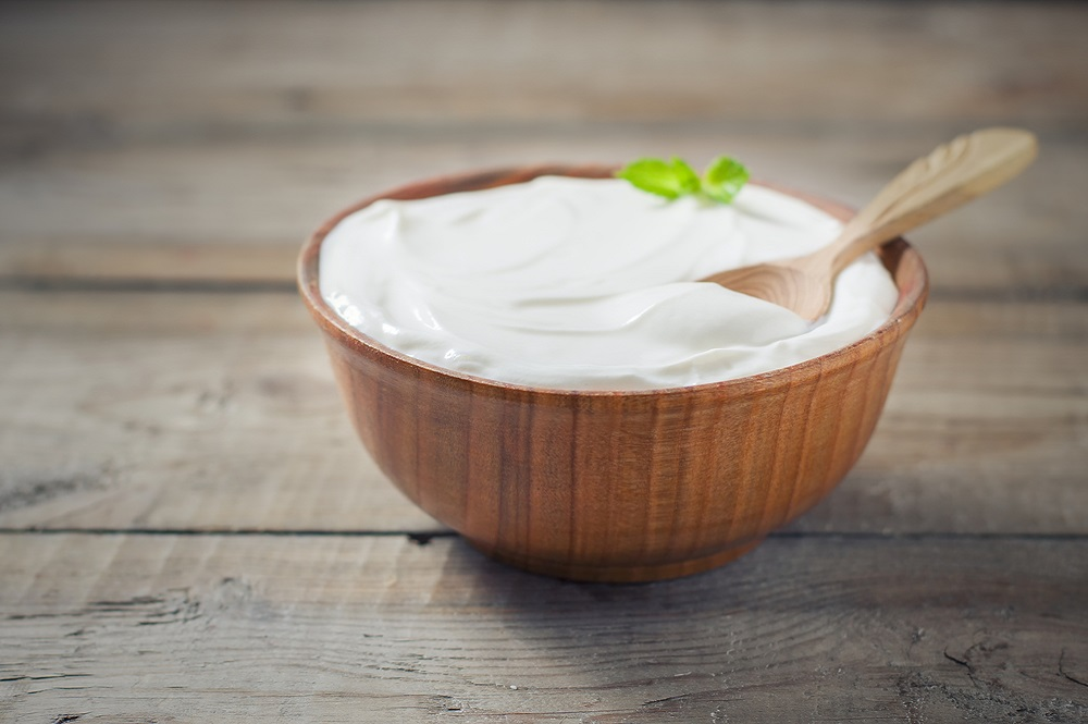 Greek yoghurt in wooden bowl on table