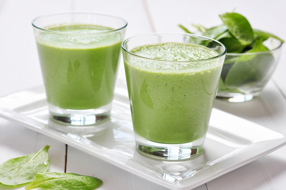Two glasses of green smoothie on a plate