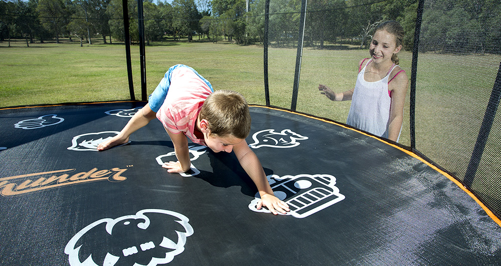 Boy playing twister on his Vuly trampoline