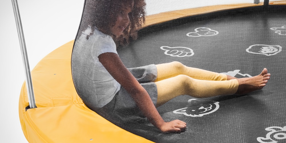 Girl sitting inside trampoline enclosure