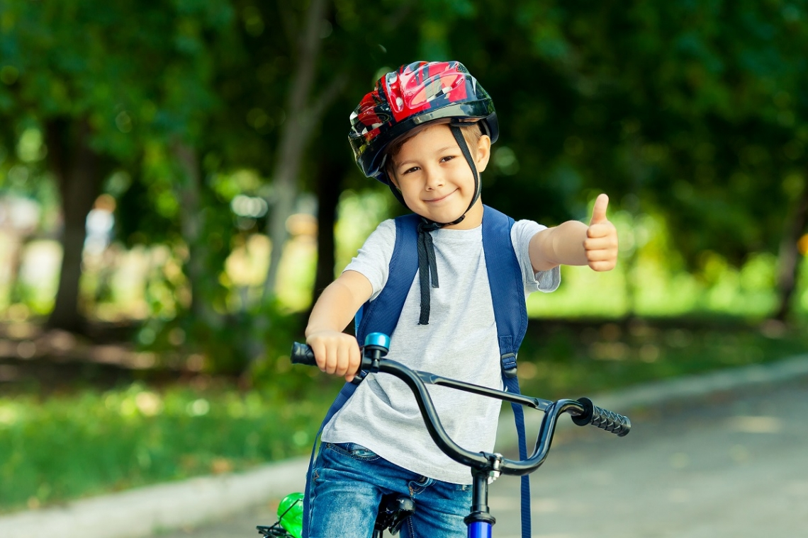 Kid on bike giving the thumbs up