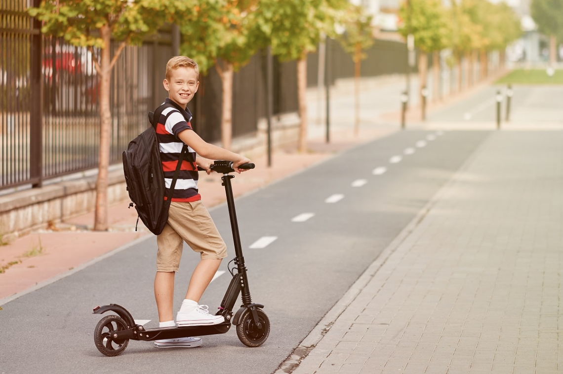 Boy standing on his electric scooter with backpack