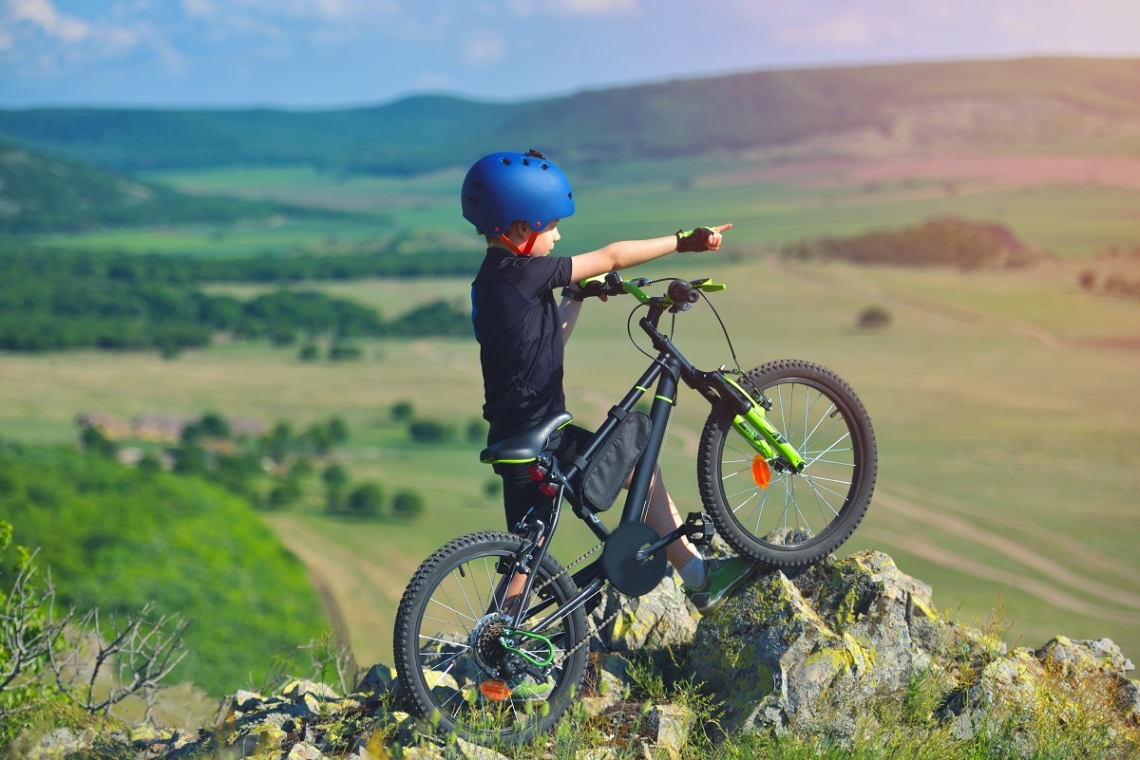 Child on his mountain bike on top of a rock hillside