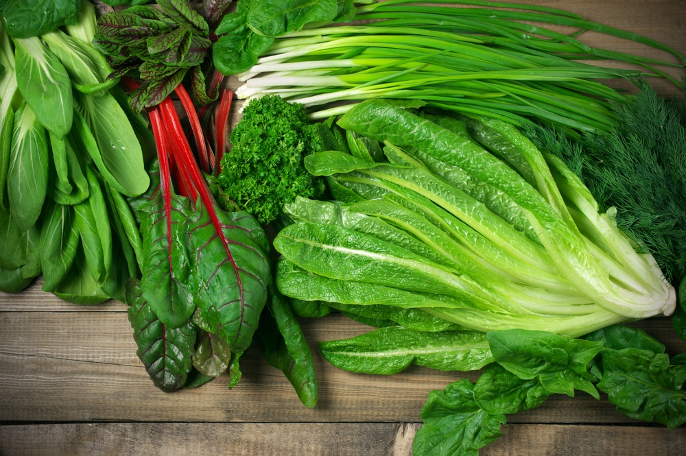 Various green leafy vegetables on wooden table