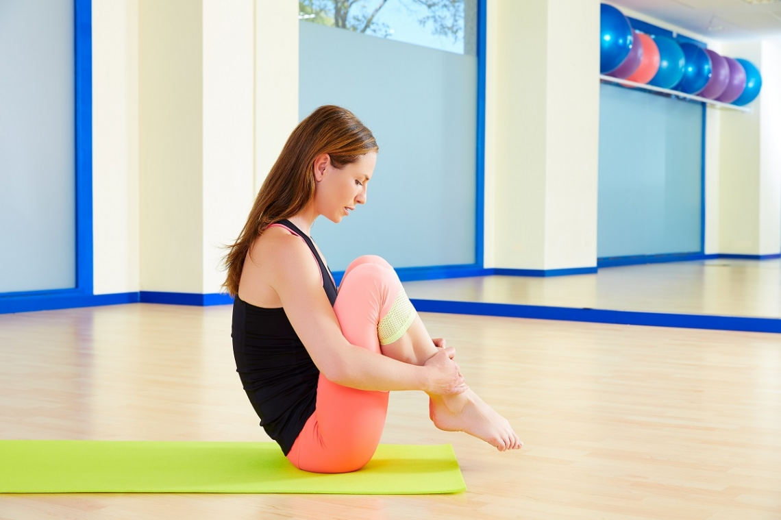 Woman attempting Pilates ball roll pose