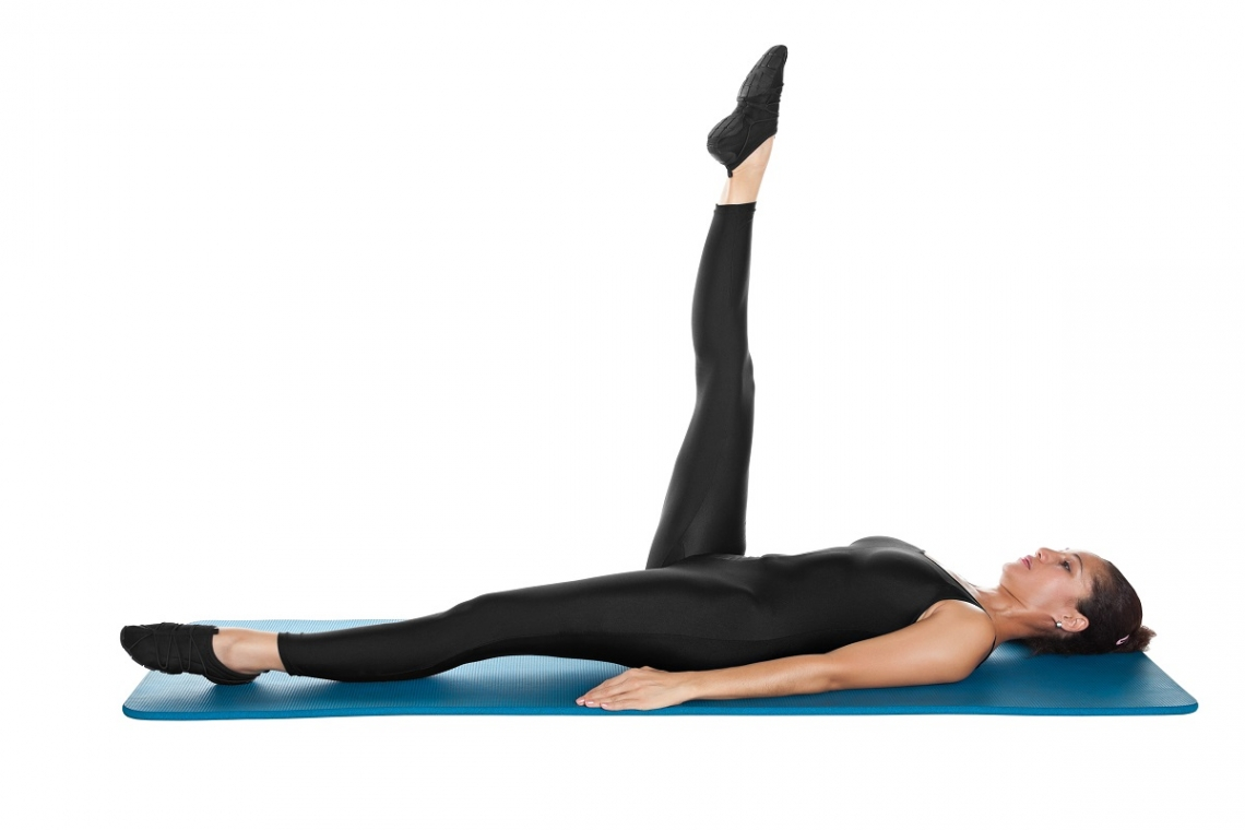 Woman on her back attempting Pilates exercise of leg circles