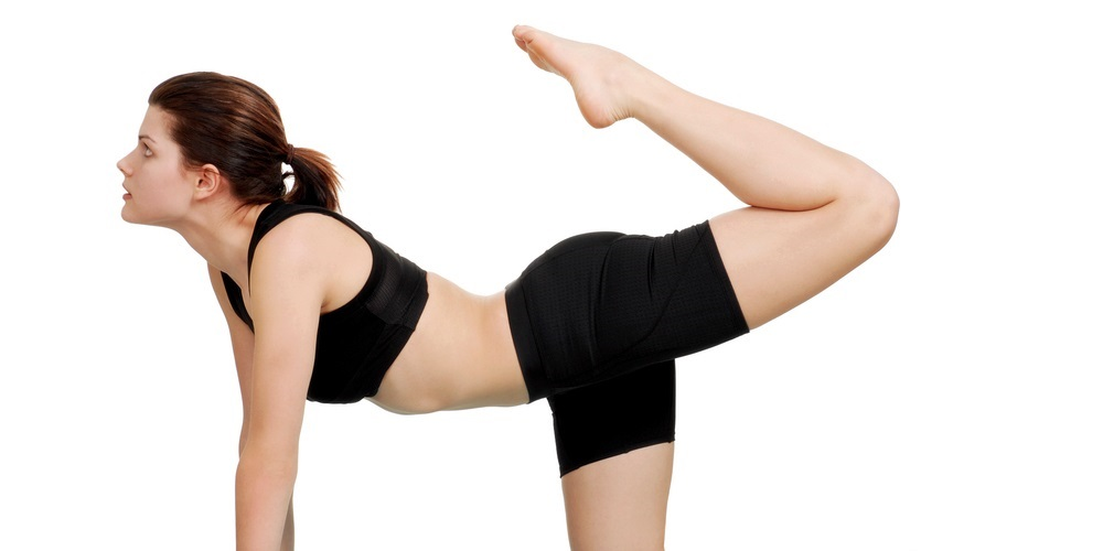Woman doing donkey kicks for Pilates exercise
