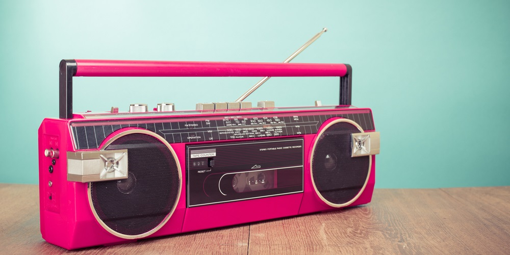 Pink radio player sitting on wooden bench
