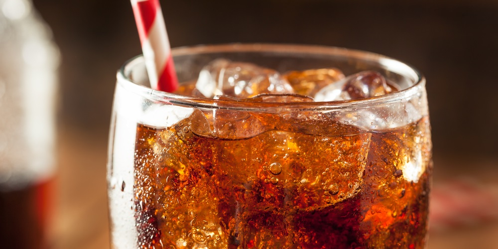 Cola soft drink in glass with striped straw