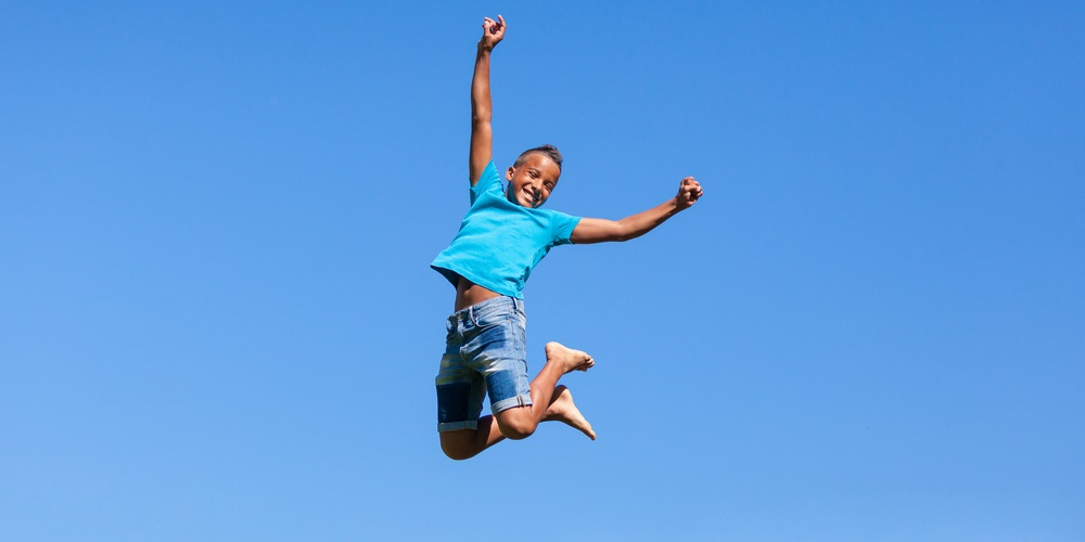 Boy bouncing up into the sky