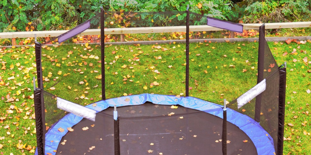 Trampoline covered in leaves in a backyard