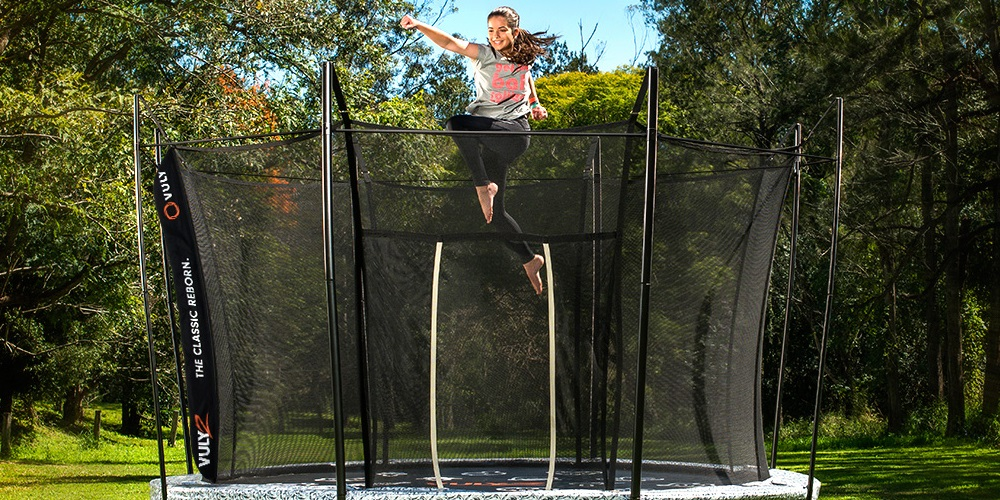 Girl bouncing on trampoline with safety netting