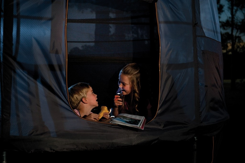 Kids camping out at night and reading with torches in a Vuly trampoline tent