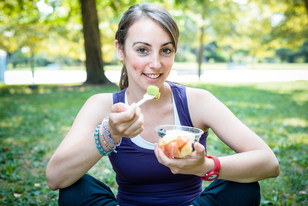 Woman eating fruit salad after running at the park