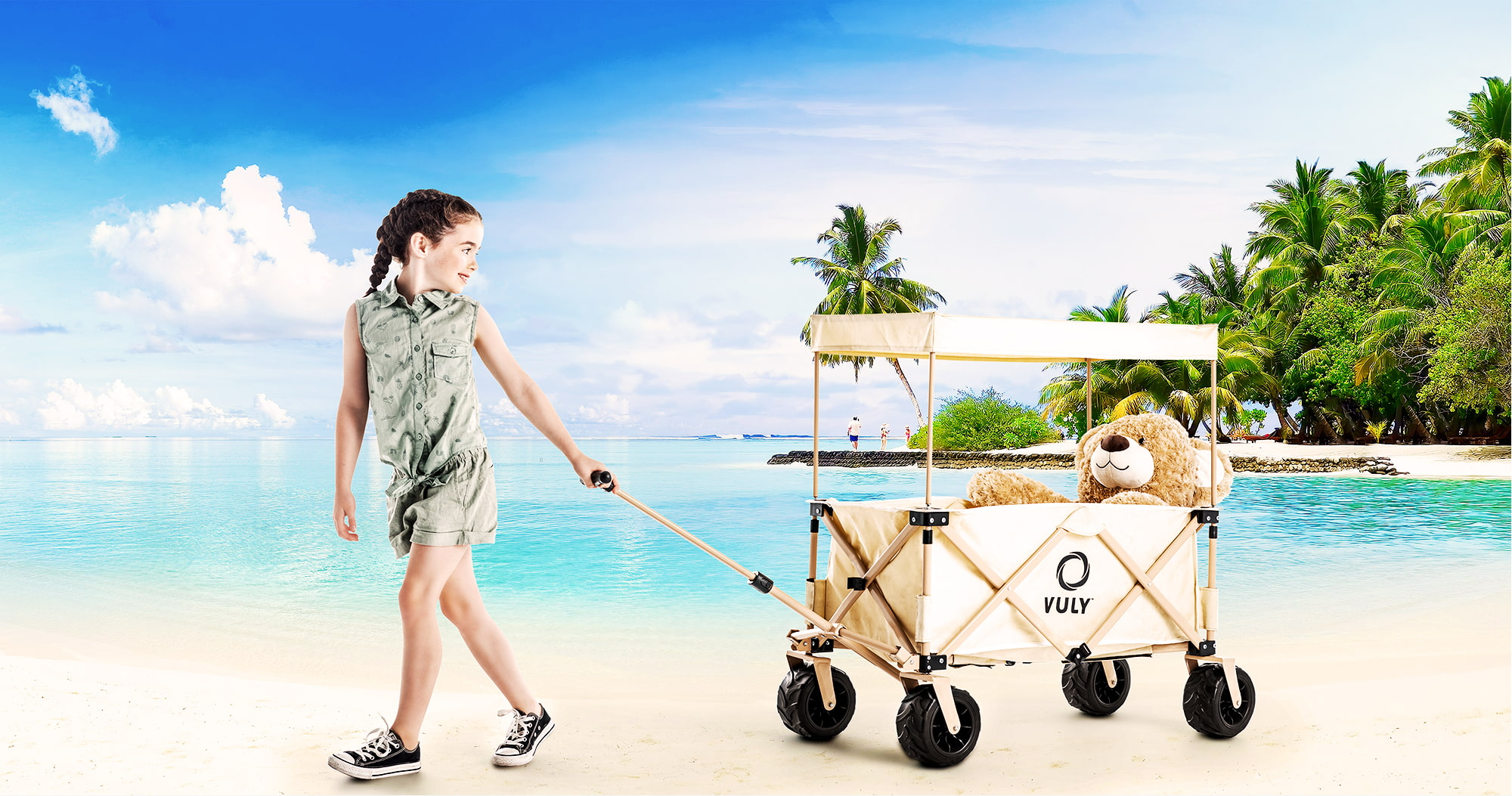 Young girl at the beach towing Rover Beach Edition Wagon Cart carrying teddy bear